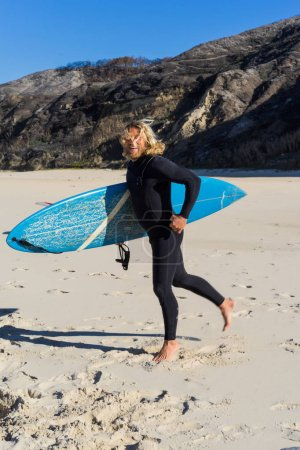 Photo for Man surfer on the beach warming up before surfing, Surf Man in a wet suit with a surfboard on the ocean, Nazar, Portugal. - Royalty Free Image