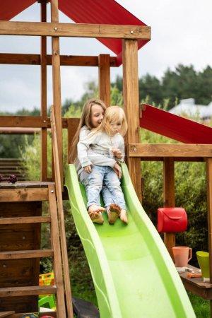 Photo pour Enfants montent de la glissière des enfants, les sœurs jouent ensemble dans le jardin, les enfants jouent et s'amusent dans la cour - image libre de droit
