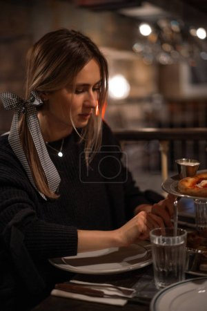 Photo for Young beautiful woman in a pizzeria eats juicy pizza. - Royalty Free Image