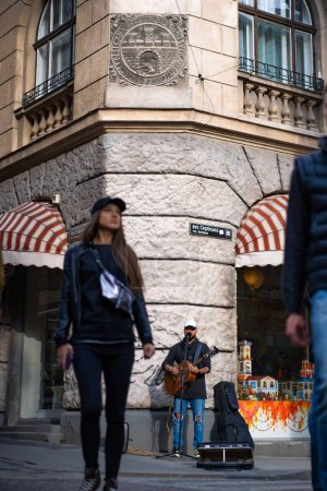 Photo for Street musician. A man plays the guitar and sings into a microphone on a city street. - Royalty Free Image