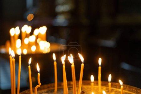 Photo pour Des bougies allumées dans une église - image libre de droit
