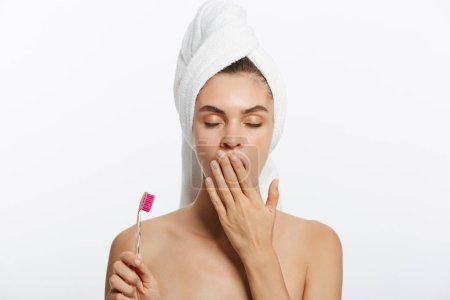 A sleepy young woman with a white towel is yawning and holding a toothbrush against a white background.