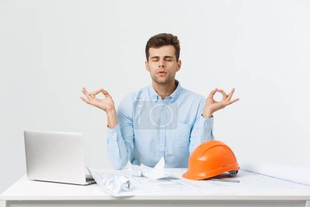Photo pour Jeune bel homme d'ingénieur ou d'un constructeur en bleu costume yoga pratique et vous détendre au bureau - image libre de droit
