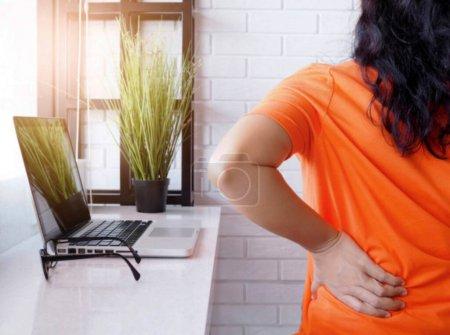 Junge Asiatin arbeitet mit Laptop-Computer und sitzt auf Stuhl und leidet unter Rückenschmerzen und Hüftschmerzen, Gesundheitskonzept und Körperschmerzen.