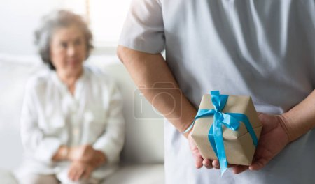Photo for Making a surprise for Christmas and New year concept. Asian Senior man hiding gift box behind his back while his wife sitting and looking to him at their house. - Royalty Free Image