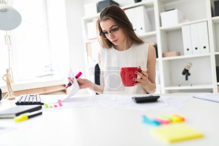 A young girl in the office holds a pink marker, a red mug and works with documents.