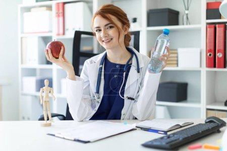 ein schönes junges Mädchen in weißem Gewand sitzt an einem Tisch im Büro und hält einen Apfel und eine Flasche Wasser in der Hand.