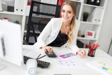 Photo pour Belle jeune fille aux cheveux blonds en une veste blanche et une blouse noire travaille dans le bureau. photo avec la profondeur de champ - image libre de droit