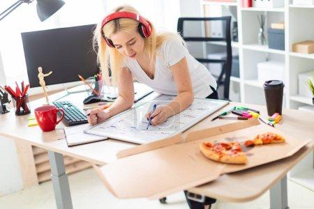 Photo pour Belle fille blonde dans un débardeur blanc et pantalon foncé. La fille écoute de la musique à travers les écouteurs rouges et travaille avec un marqueur et un tableau magnétique dans une armoire lumineuse. photo avec profondeur de - image libre de droit