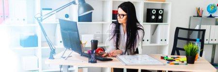 Photo pour Une jeune fille aux lunettes, vêtue d'un chemisier blanc et d'un pantalon noir, travaille au bureau. La fille a de longs cheveux noirs. photo avec profondeur de champ - image libre de droit