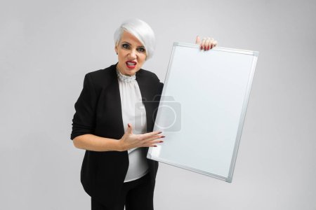 Photo for Young woman holding white board. Pretty business woman holding a white blank board over white background. Businesswoman presenting sign against - Royalty Free Image