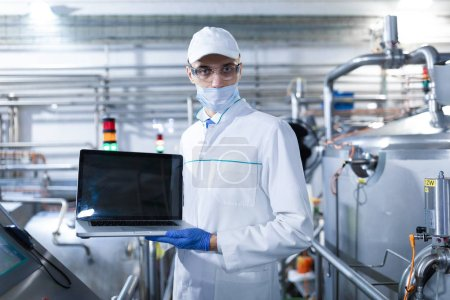 Photo for Technologist in a white coat with a laptop in his hands controls the production process in the dairy shop. Place for writing. Technologist with a laptop computer is at the factory - Royalty Free Image