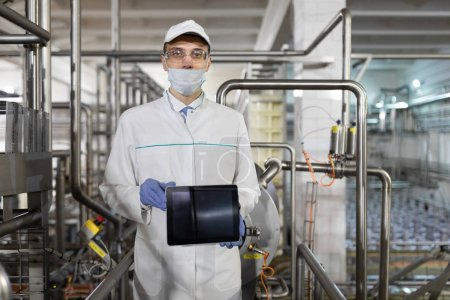 Photo for Technologist in a white coat with a tablet in his hands is in the shop for the production of butter and cheese. The production process at the plant of dairy products. A place for a label - Royalty Free Image