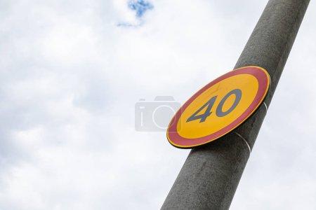 Photo pour Vue inférieure de la limite de vitesse européenne de signalisation routière quarante contre le ciel nuageux - image libre de droit