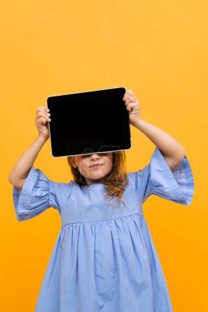 Photo pour Mignonne petite fille avec tablette posant sur fond orange - image libre de droit
