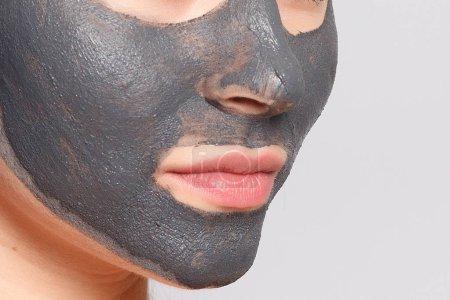 Photo pour Masque de femme. Portrait Of Beautiful Girl enlevant noir cosmétique Peeling masque de peau du visage. Gros plan d'une jeune femme séduisante avec maquillage naturel et cosmétique Peel masque sur le visage. Haute résolution - image libre de droit
