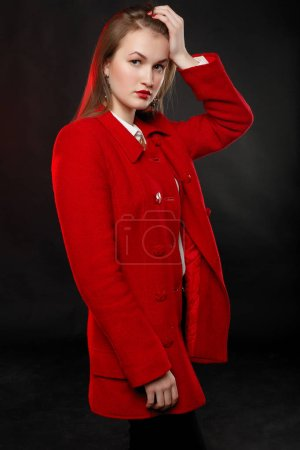 Photo for Fashionable woman in bright red coat and white shirt, with a gold necklace posing in studio, looking at camera. cold season. Autumn or winter look. - Royalty Free Image