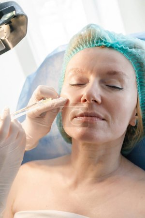 Photo pour Docteur esthéticienne fait des injections dans le front pour la beauté du patient. Injections de beauté en cosmétologie. La notion de beauté. - image libre de droit