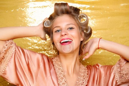 Photo for Beautiful Smiling girl in hair curlers isolated on gold. Portrait of young beautiful sexy smiling woman - Royalty Free Image