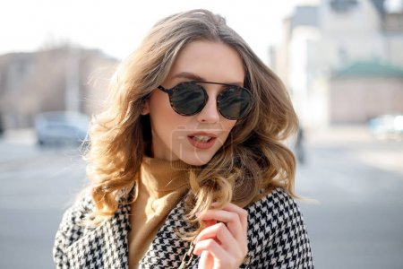 Photo for Attractive girl in a coat in the street in a city, sun is shining, than turns to camera and smiles. portrait happy slow motion summer face sunset beautiful lady outdoor closeup cute - Royalty Free Image