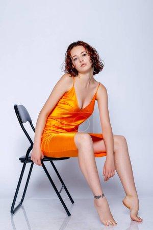 Foto de Retrato de chica atractiva en vestido naranja en el estudio. Fascinante dama pelirroja. primer plano retrato sentado en una silla - Imagen libre de derechos