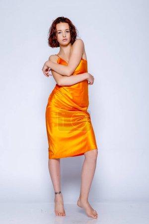 Foto de Retrato de chica atractiva en vestido naranja en el estudio. Fascinante dama pelirroja - Imagen libre de derechos