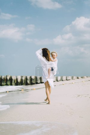 Photo for Young mother and happy little son at sandy beach in Dubai, UAE - Royalty Free Image