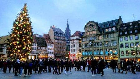 Photo pour Place animée de Strasbourg, France pendant le mois de mars de Nol (Strasbourg), marché de Noël le plus populaire d'Europe. Les habitants et les touristes sont regroupés et sont entassés autour du sapin de Noël géant au milieu de la place de la ville de Strasbourg. - image libre de droit