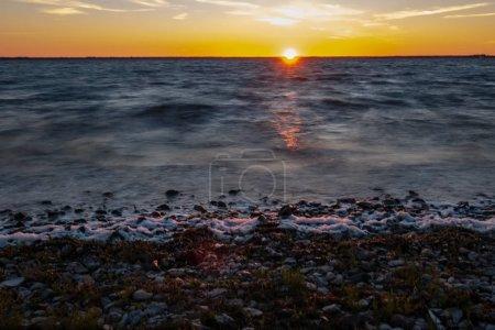 dramatic sunrise over the baltic sea with rocky beach and trees on the shore. long exposure shot. Estonia, Hiiumaa island