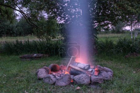 woods are burning in fireplace, warm, heat, fire in darkness. long exposure image with motion blur. camping in nature in summer