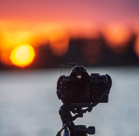 Photo pour Appareil photo numérique sur un trépied prenant des photos du coucher du soleil sur le lac. hobby photographie - image libre de droit