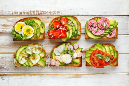 Photo for Avocado sandwiches, toasts with various vegetarian toppings on a white wooden table, top view - Royalty Free Image
