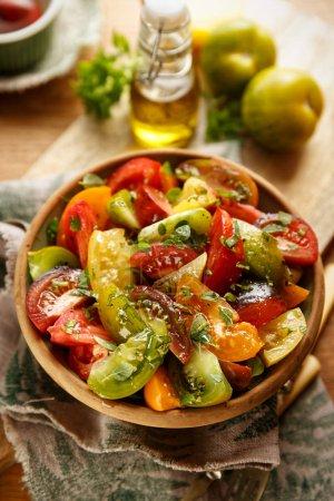 Photo pour Salade de tomates avec basilic frais d'ajout, de l'huile d'olive et d'épices. Aliments végétaliens avec des produits de culture biologique. Concept de la saine alimentation - image libre de droit