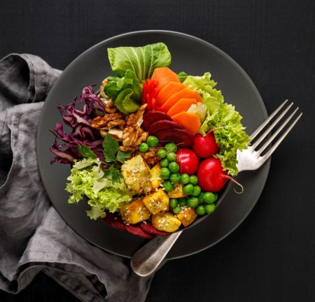 Photo for Buddha bowl,  healthy and nutritious salad with a variety of vegetables, nuts and tofu cheese,delicious and nutritious vegan meal, top view - Royalty Free Image