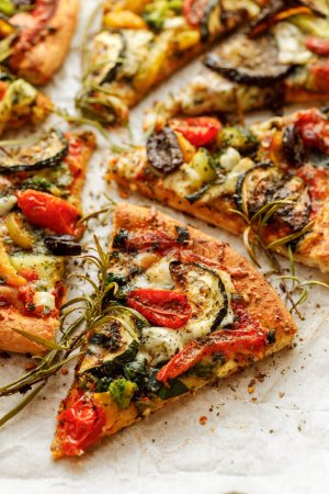 Photo for Vegetarian pizza with addition grilled vegetables and aromatic herbs, divided into portions - Royalty Free Image