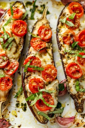 Photo for Grilled eggplants, stuffed with cheese and cherry tomatoes sprinkled chopped basil  on white background, close up - Royalty Free Image