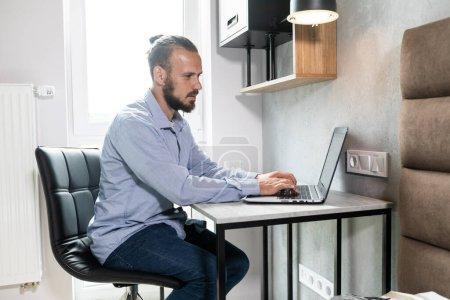 El tipo se sienta en el ordenador y mira el monitor del ordenador portátil y responde al correo electrónico