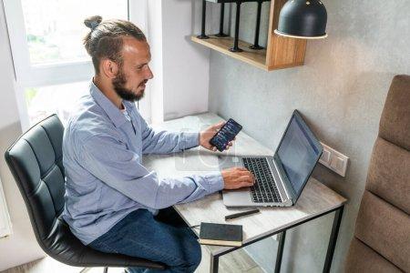 El tipo se sienta en el ordenador, mira el teléfono y responde a los mensajes