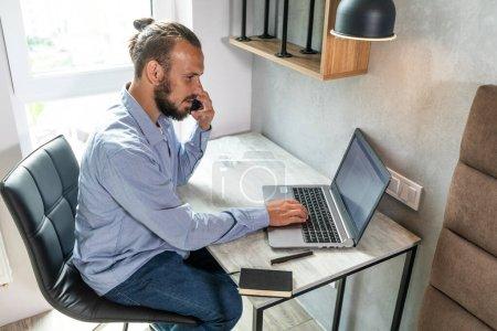 El tipo se sienta en el ordenador, mira el teléfono y responde a la llamada
