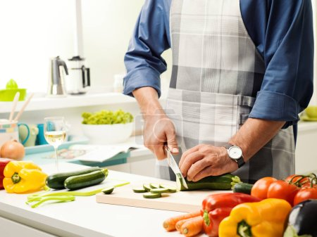 Photo for Man preparing lunch in the kitchen, he is slicing fresh healthy vegetables on the chopping board, healthy food concept - Royalty Free Image