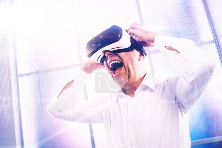 Cheerful mature man wearing a VR headset and interacting with a virtual reality environment