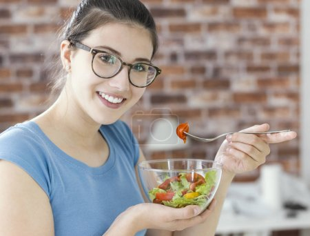 Photo for Happy young woman eating fresh salad in a bowl, healthy vegan food and dieting concept - Royalty Free Image