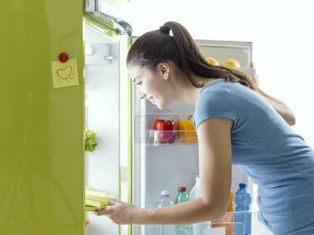 Photo for Smiling woman taking some fresh celery from the fridge and preparing an healthy meal at home - Royalty Free Image