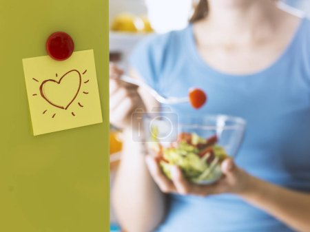 Photo for Woman eating some fresh salad next to the fridge, healthy vegan food and dieting concept - Royalty Free Image