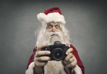 Photo for Happy surprised Santa Claus holding a camera and shooting holiday pictures for Christmas - Royalty Free Image