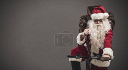 Photo for Santa Claus carrying a heavy sack with gifts for Christmas and riding a bicycle, banner with blank copy space - Royalty Free Image