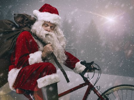 Photo for Santa Claus riding a bicycle and carrying a heavy sack with gifts for Christmas under the snow - Royalty Free Image
