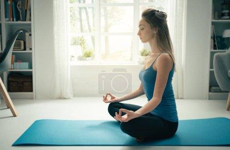 Photo pour Jeune femme confiante pratiquant méditation attentive à la maison, elle est assise avec les jambes croisées sur un tapis - image libre de droit