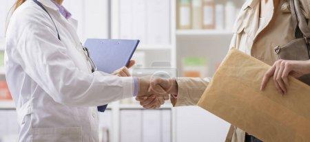 Photo pour Patiente rencontrant le médecin au bureau, ils se serrent la main et saluent - image libre de droit