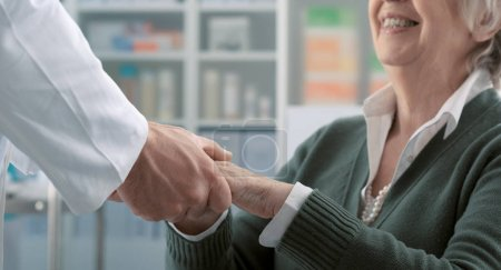Photo for Friendly professional doctor holding a senior patient's hands and supporting her: care, assistance and medicine concept - Royalty Free Image